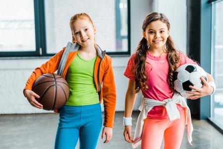 Niños sonrientes en ropa deportiva sosteniendo pelotas en el gimnasio