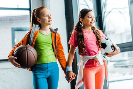 Blissful kids holding hands while posing in gym