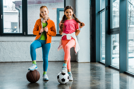 Confident kids posing with balls in gym