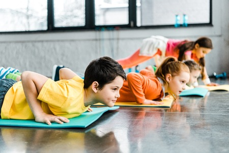 Preteen kids doing push-up exercise in gym Standard-Bild - 119522773