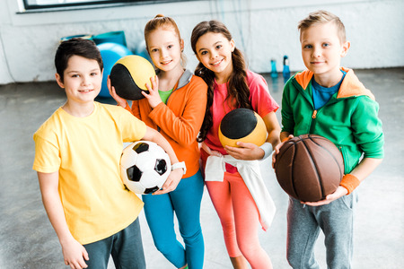 Excited children in sportswear posing with balls Imagens