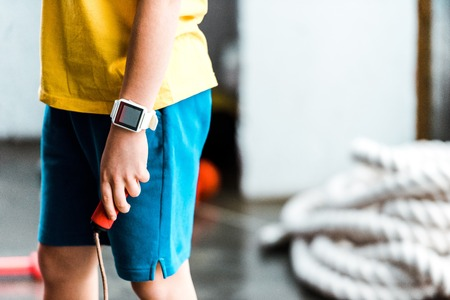 Partial view of boy in smartwatch holding jump rope