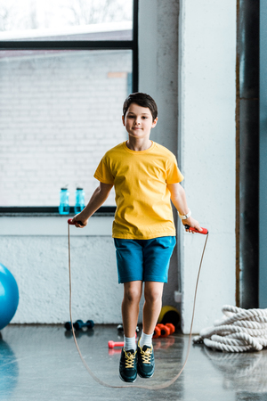 Brunette boy in yellow t-shirt jumping with skipping rope