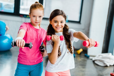 Active kids doing exercise with dumbbells in gym Banco de Imagens