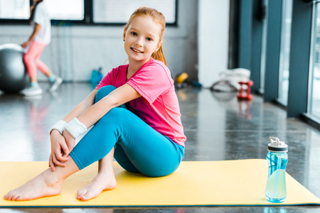 Barefooted kid sitting on yellow fitness mat with smile