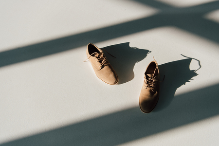 pair of beige suede shoes on floor in sunlight with shadows