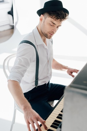 handsome pianist in white shirt and black hat playing piano