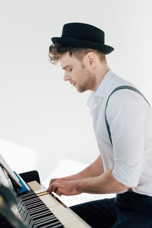 concentrated pianist in stylish clothing playing piano
