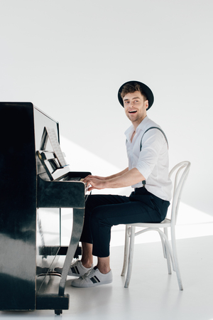 inspired pianist in white shirt and black hat playing piano