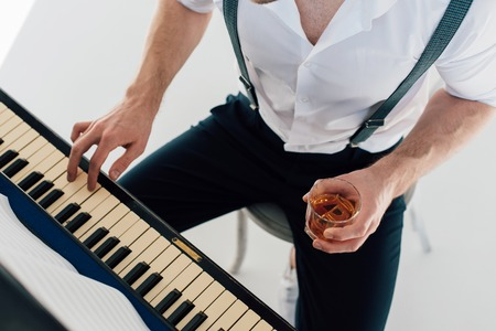 cropped view of pianist holding glass of alcohol drink while playing piano Stockfoto