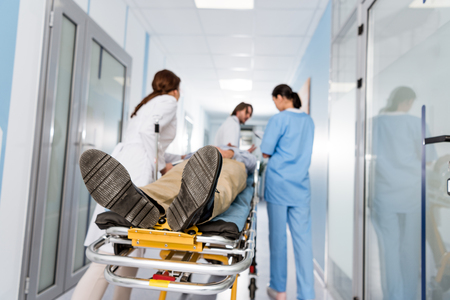 Doctors in uniform transporting patient to operating room