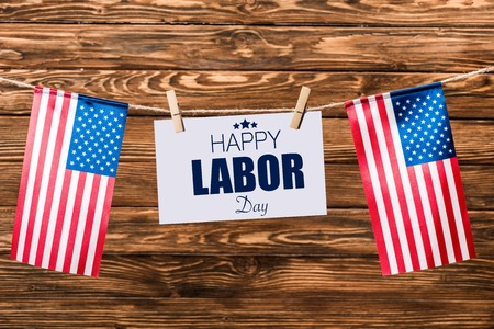 card with happy labor day lettering hanging on string with pins and american flags on wooden background