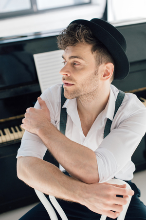 selective focus of dreamy composer in white shirt and black hat Фото со стока