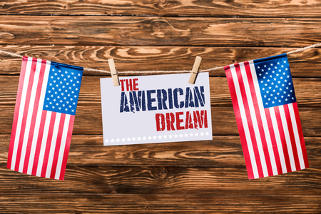 card with the american dream lettering hanging on string with pins and american flags on wooden background