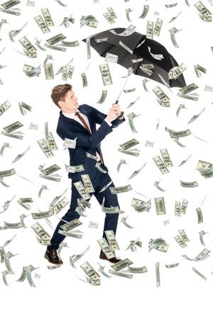 successful businessman in suit holding umbrella under money rain on white background