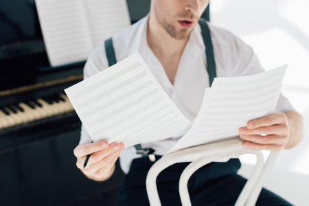 selective focus of man holding music book sheets Foto de archivo - 119527139