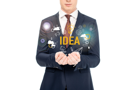 cropped view of businessman in suit with outstretched hands and idea lettering and icons above isolated on white
