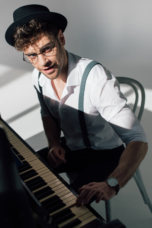 smiling musician in spectacles playing piano and looking at camera