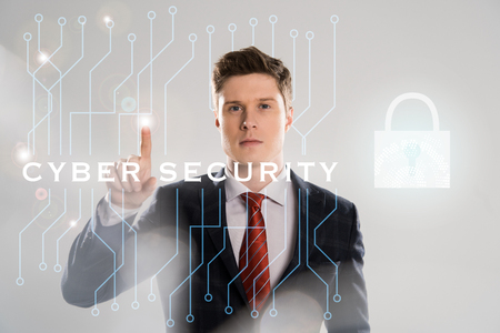 confident businessman in suit pointing with finger at cyber security illustration in front