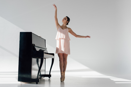 graceful ballerina dancing near black piano