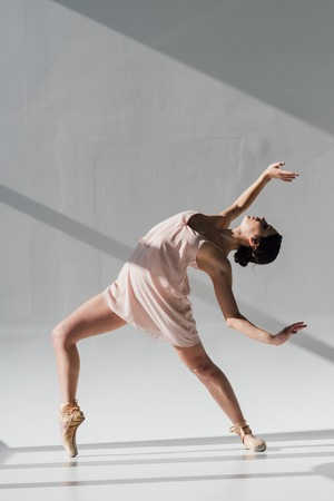 young ballerina dancing in pink dress and pointe shoes