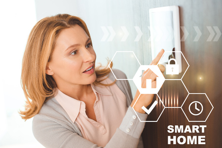 pretty blonde woman using smart house system control panel
