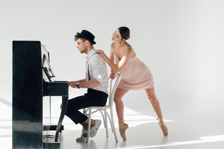 handsome pianist playing piano while young ballerina touching his shoulder