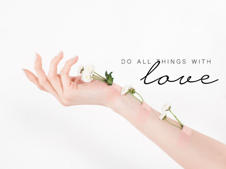 cropped view of woman with wildflowers on hand on white background with do all things with love illustration