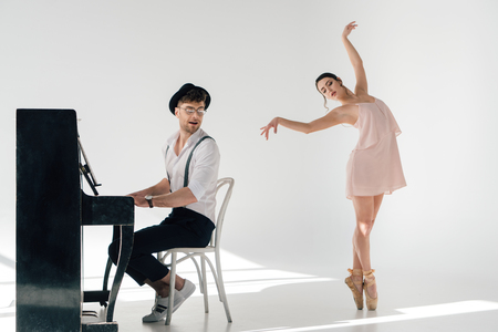 musician playing piano while attractive ballerina dancing near him Foto de archivo - 119528974