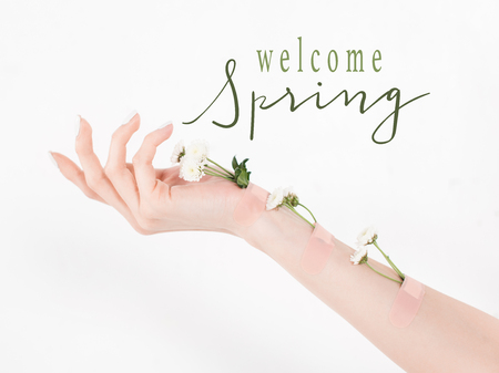 cropped view of woman with wildflowers on hand on white background with welcome spring illustration