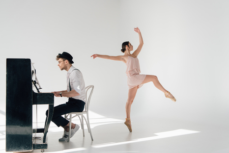 handsome pianist playing piano while young ballerina dancing in pink dress