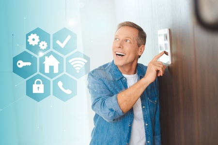 happy handsome man using smart house system control panel Фото со стока