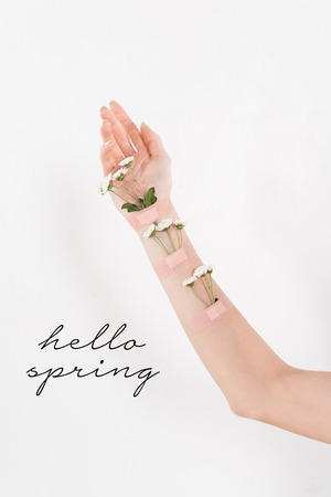 cropped view of woman with wildflowers on hand on white background with hello spring illustration 스톡 콘텐츠