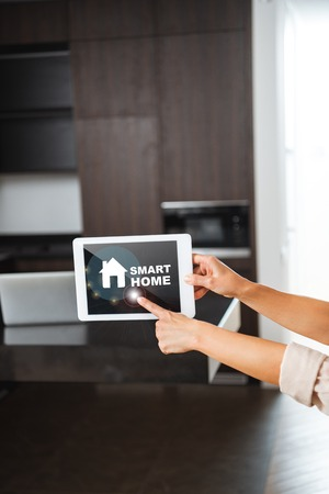 selective focus of female hands with digital tablet with smart home illustration