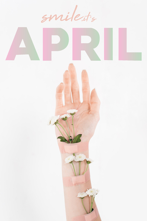 cropped view of woman with wildflowers on hand on white background with april illustration