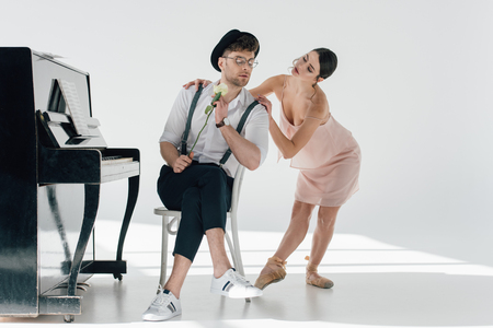 handsome musician holding rose while young ballerina touching his shoulders o Banque d'images