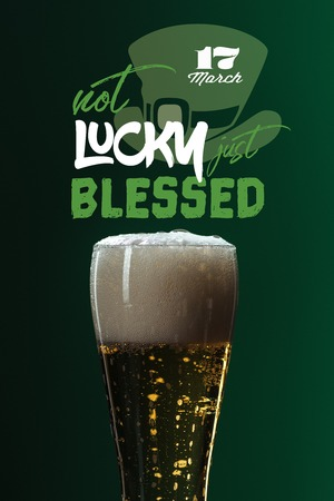 beer glass with foam near not lucky just blessed lettering on green background
