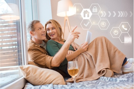 happy wife holding digital tablet while resting with husband under cozy fleece blanket, smart home concept