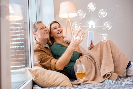 smiling wife holding digital tablet while sitting on floor with husband, smart home concept