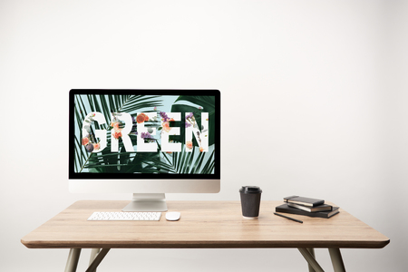 computer with green leaves and green lettering on monitor on wooden desk