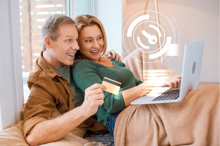 excited wife pointing at laptop screen while husband holding credit card, smart home concept