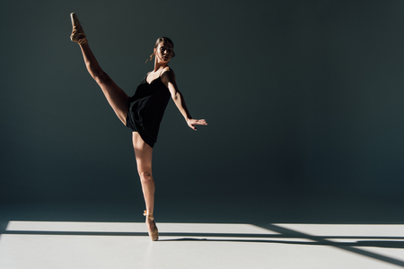 attractive ballerina dancing in black dress and pointe shoes Stockfoto