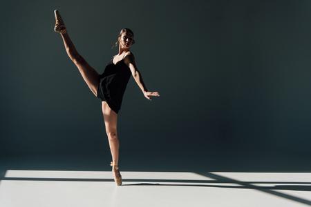 attraente ballerina che balla in abito nero e scarpe da punta Archivio Fotografico