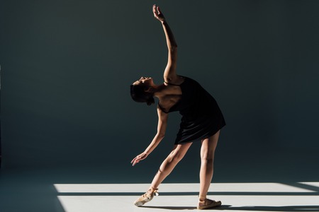 graceful young ballerina in black dress dancing in sunlight Фото со стока