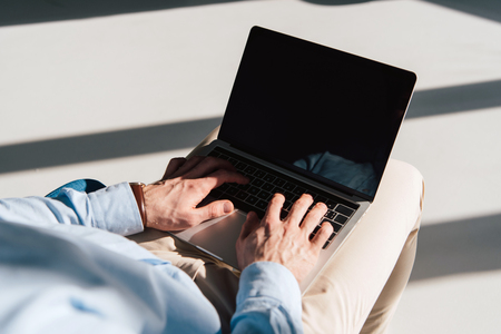 selective focus of man using laptop with blank screen