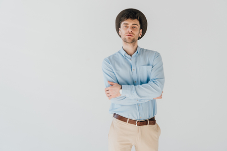 serious man in blue shirt and beige jeans looking at camera isolated on grey Stock Photo