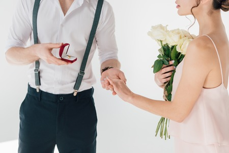 cropped view of man making marriage proposal to girl with bouquet of roses
