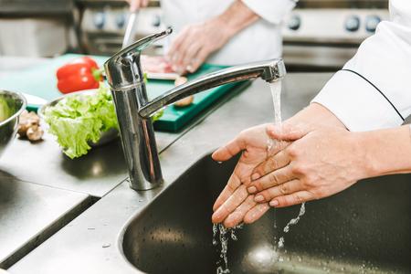 Vista recortada de la mujer chef lavarse las manos sobre el fregadero en la cocina del restaurante