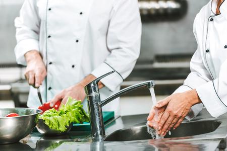 Vista recortada de la mujer chef lavarse las manos sobre el fregadero mientras su colega cocina en el fondo en la cocina del restaurante Foto de archivo