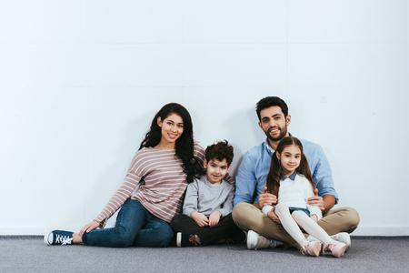 Feliz familia hispana sentada en el piso cerca de la pared blanca